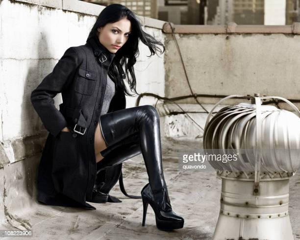 美しいセクシーなヒスパニック系ファッションのモデルにブーツの屋上