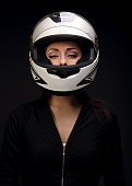Beautiful sexy makeup woman looking in white motorcycle helmet on black background. Closeup dark portrait