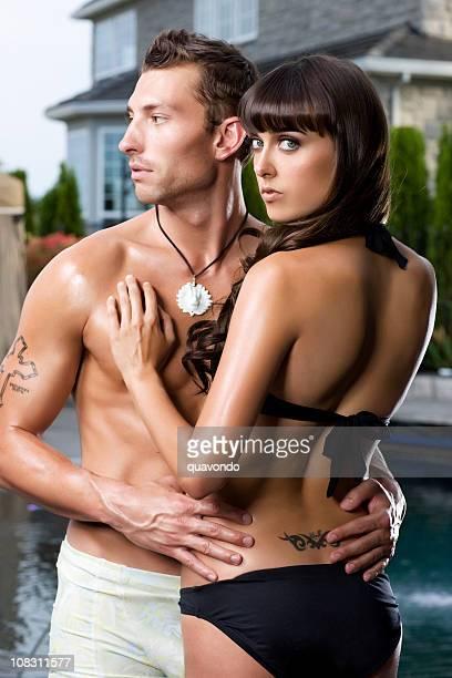 Cuoio giovane coppia bella Sexy in costume da bagno accogliere a bordo piscina