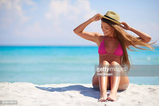 Beautiful sexy woman sitting on the beach over sea background