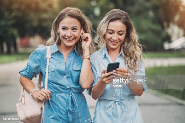 Beautiful sisters with smart phone and headphones