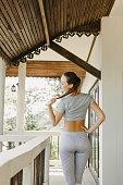 beautiful slim sportswoman in yoga pants standing on porch