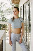 beautiful slim woman in sportswear standing on porch