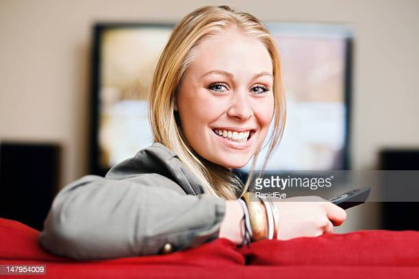 Beautiful smiling blonde, sofa, television: happiness!