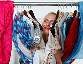 Beautiful smiling blonde woman standing inside wardrobe rack full of clothes happy to have it. Shopping and consumerism or stylist concept. Nothing to wear and hard to decide concept