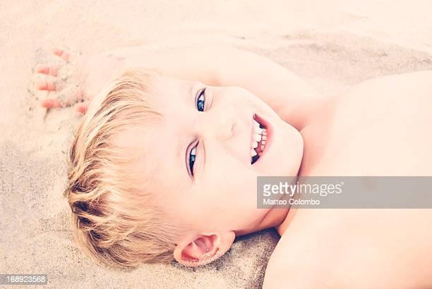 Beautiful smiling child laying on sand beach