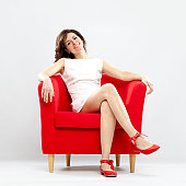 Beautiful smiling girl relaxed on red armchair