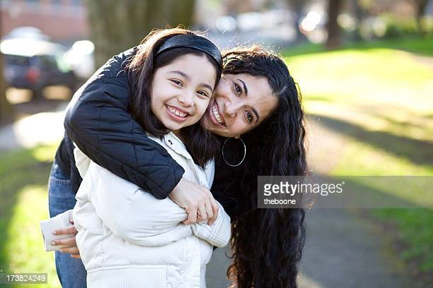 beautiful smiling hispanic mother and daughter hugging in a park
