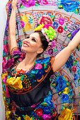 beautiful smiling mexican woman in traditional mexican dress nands up holding the skirt as a background like peacock