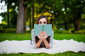Beautiful smiling modern young girl student in casual clothes reading a book lying on a plaid in a city park