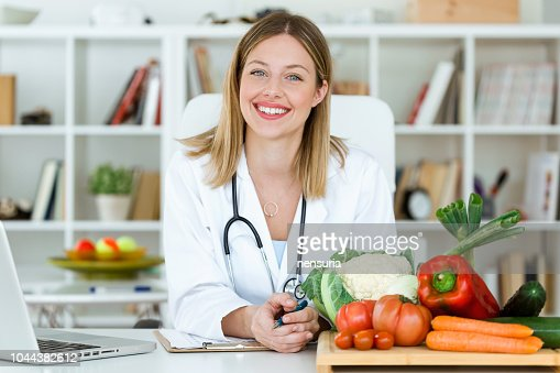 Beautiful smiling nutritionist looking at camera and showing healthy vegetables in the consultation. : Foto de stock