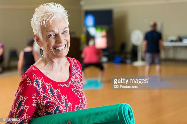Beautiful smiling senior woman before yoga class