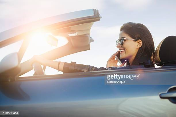 beautiful smiling woman in the car talking on the phone