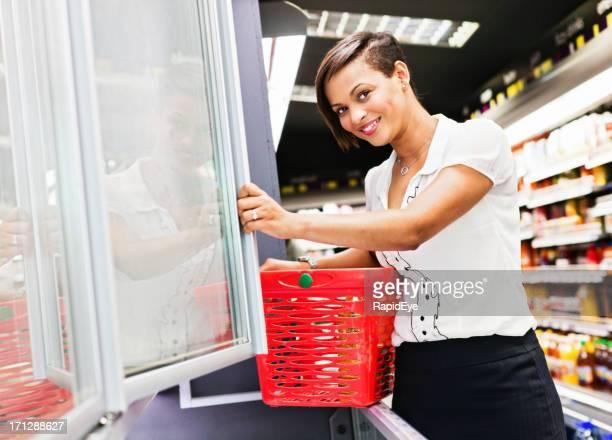 Beautiful smiling woman reaches into supermarket fridge