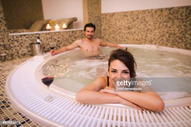 Beautiful smiling woman relaxing in jacuzzi at health spa.