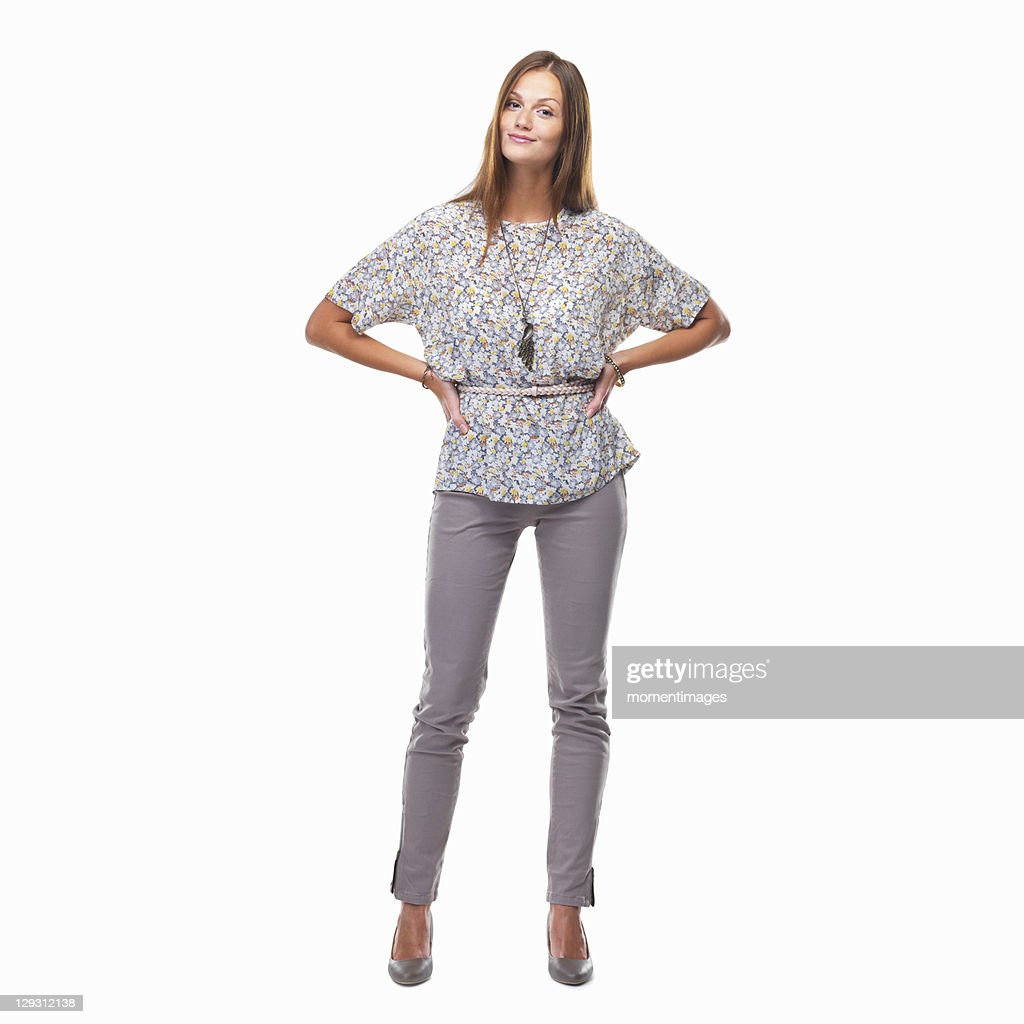 Beautiful smiling woman standing with hands on hips against white background