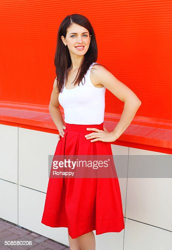 Beautiful smiling woman wearing a red skirt over colorful background : Bildbanksbilder