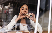 Portrait of beautiful smiling young woman eating sandwich in cafe. Cafe window