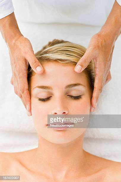Beautiful smiling young woman receiving head massage