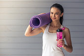 Beautiful young woman in sports wear is holding a yoga mat and a bottle of water, looking at camera and smiling, standing on a gray background