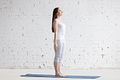 Attractive happy young woman working out indoors. Side view portrait of beautiful model doing yoga exercise on blue mat. Standing in Tadasana, Mountain Pose. Full length