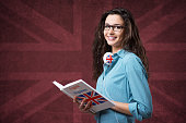 Beautiful student girl posing with an open book and smiling
