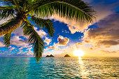 The sun rises over the beautiful Mokes on the shores of Lanikai Beach in Kailua, Oahu.