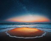 Beautiful sunrise over the sea and milky way