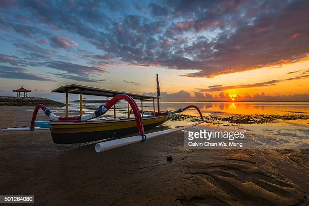 A beautiful sunrise with local spider boat in foreground at Karang beach - Sanur