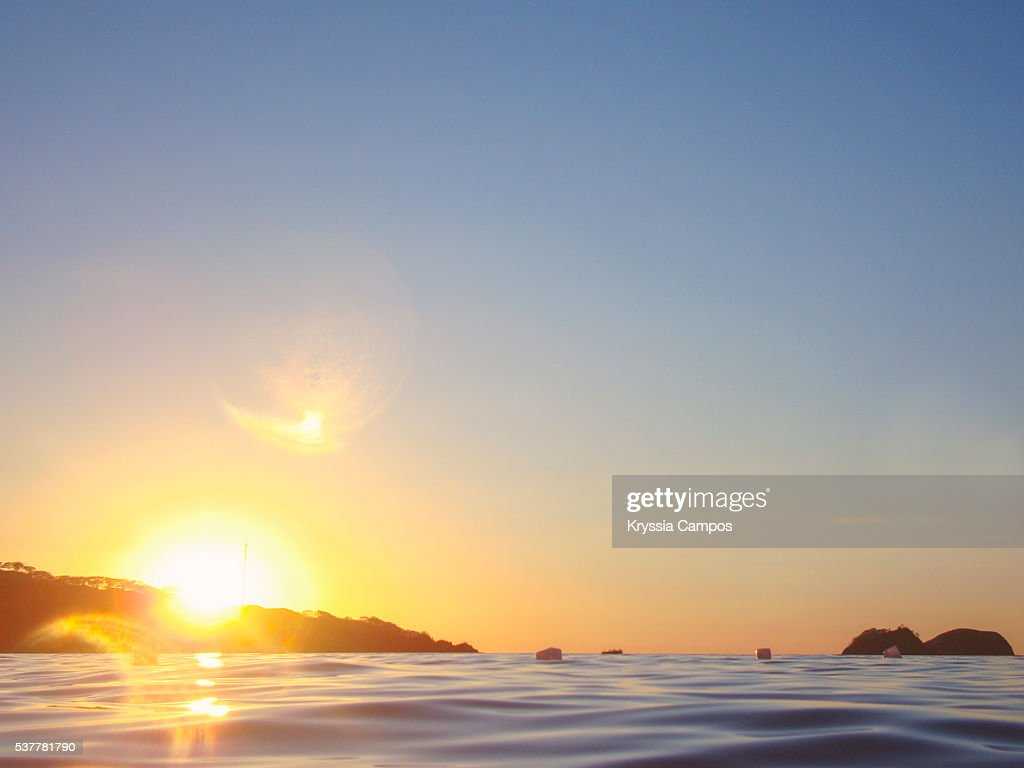 Beautiful sunset at sea level with lens flare : Stock Photo