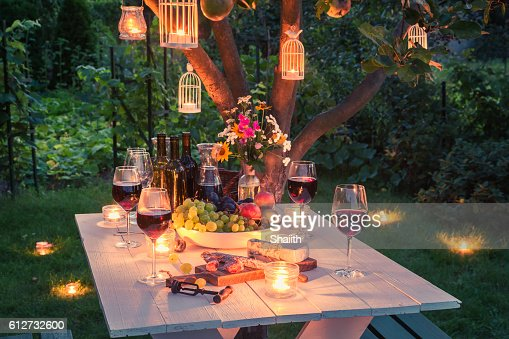 Beautiful table full of cheese and meats in garden : Stock Photo