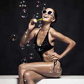 Beautiful Tan Female Model Posing In Bikini And Blow Bubbles. Against Black Wall.