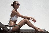 Beautiful tan female model sunbathing in bikini on chaise-longue. Against white wall.