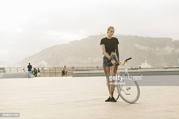 Beautiful Tattooed Woman Riding on a Bicycle In Golden Sunset