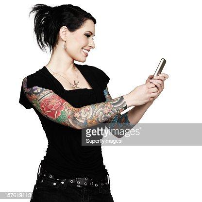 美しい笑顔 tattooed 女性の携帯電話を使用しています。白の背景。