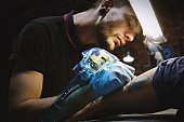 Beautiful tattooist with tunnels makes a tattoo on his leg