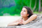 Beautiful biracial  teen girl on tropical  beach praying by driftwood log