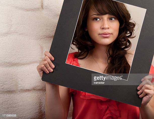 Schöne junge Brunette mit Spähen durch Papier Bilder
