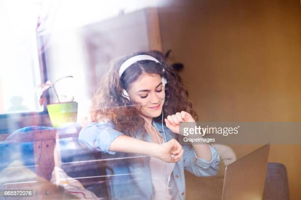 Beautiful teenage girl at home sitting on couch, laptop on her lap, wearing headphones, listening music. Look through window.