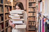 Beautiful teenage girl hiding behind a stack of books