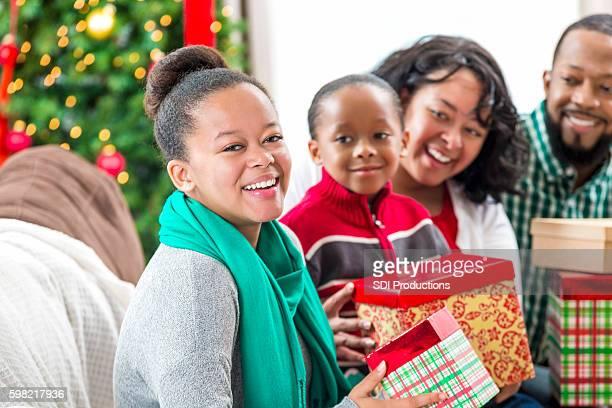 Beautiful teenage girl opens gift on Christmas Eve
