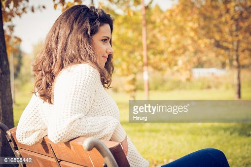 Beautiful teenage girl sitting in the park : Stock Photo