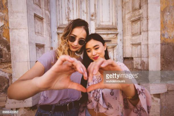 Beautiful teenage girls making a heart shape with their hands