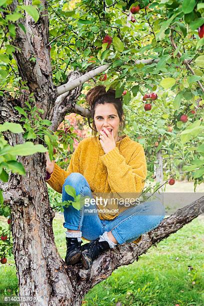 Beautiful teenager eating apple sitting on a tree branch.