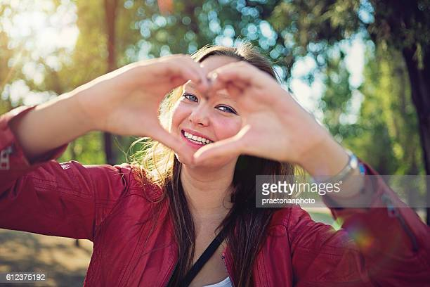 Beautiful teengirl is making heart with her hands
