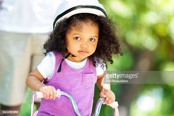 Beautiful toddler girl on a tricycle in the park