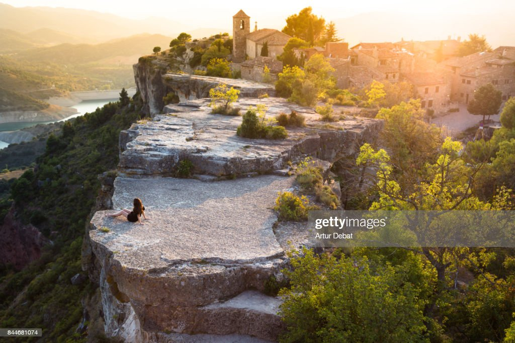 Beautiful traveler woman contemplating the view from the stunning Siurana town on top of cliff with amazing views during travel vacations in the Catalonia region. : Stock Photo