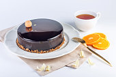 Beautiful truffle cake with orange covered with glossy dark chocolate glaze. Concept design pastry desserts