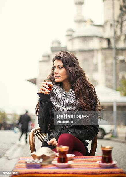 Beautiful Turkish Brunette Enjoying Tea In A Sidewalk Cafe