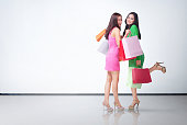 Beautiful two asian girls with colorful shopping bags posing over white wall background